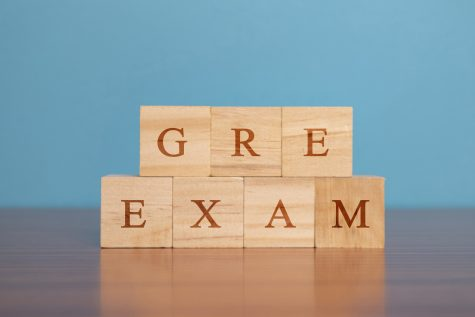 Concept of GRE Exam in wooden block letters on table.