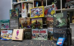 """A shelf of board games is shown from the inside of the board cafe, Fortuna in Iowa City on Sept. 29, 2021. These are a few of many games that Fortuna is planning on having in their inventory, hoping to games suited for everyone to enjoy playing. Store manager, Ryan Graham said that the cafe """"is supposed to be a happy place, somewhere to not be taking yourself so serious"""". (Larry Phan/The Daily Iowan)"""