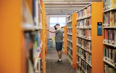 A masked visitor picks out a book at the Iowa City Public Library on Monday, Sept. 27, 2021.
