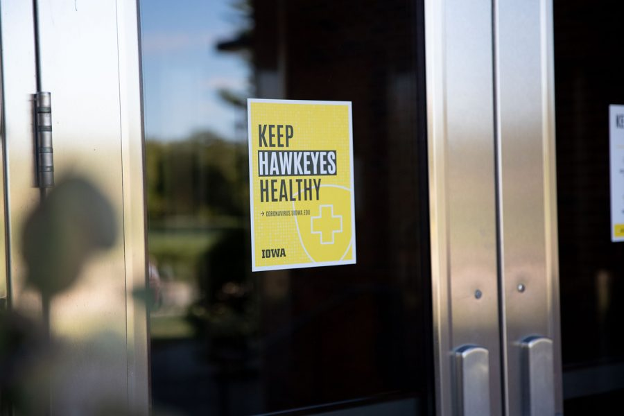 A COVID-19 safety sign hangs on the door of the Adler Journalism Building in Iowa City on Thursday, Sept. 23, 2021.