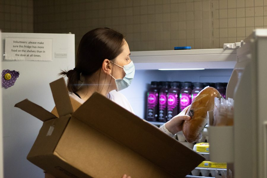 Sarah Henry puts food in the fridge at the University of Iowa Food Pantry Monday, Sept. 13, 2021.