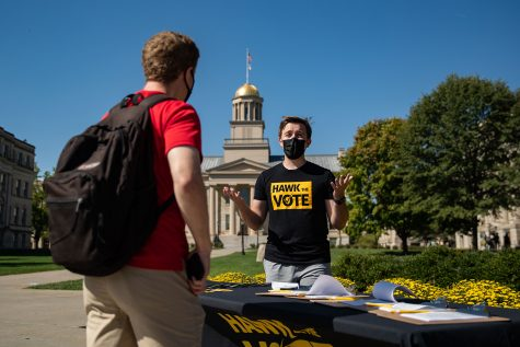 Hawk the Vote executive director Joseph Verry talks to a community member about voter registration on the Pentacrest on Tuesday, Sept. 28, 2021. Hawk the Vote wants to get people registered for the upcoming city council election.