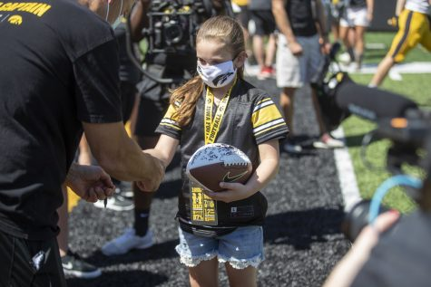 "Iowa head coach Kirk Ferentz signs a ball for kid captain Braelynn Krisinger during ""Kid's Day at Kinnick"" inside Kinnick Stadium on Saturday, Aug. 14. (Jerod Ringwald.The Daily Iowan)"