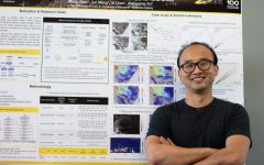 University of Iowa graduate research assistant Meng Zhou poses in front of his research Wednesday, Sept. 15, 2021.