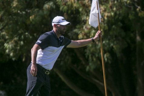Iowa head coach Tyler Stith grabs a flag out of the 18th hole during a tournament at the Donald Ross Course at the Cedar Rapids Country Club in Cedar Rapids on Tuesday, Sept. 19, 2017.