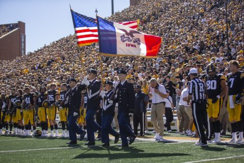 The American flag and the state of Iowa flag are presented before a game during a football game between Iowa and Colorado State at Kinnick Stadium on Saturday, Sept. 25, 2021. The Hawkeyes defeated the Rams 24-14.