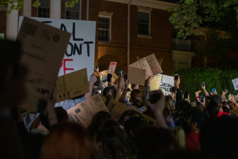 Protesters wave signs in the street during the second night of protests following sexual assault allegations against the University of Iowa's chapter of Phi Gamma Delta at the President's Residence on Wednesday, Aug. 31, 2021.