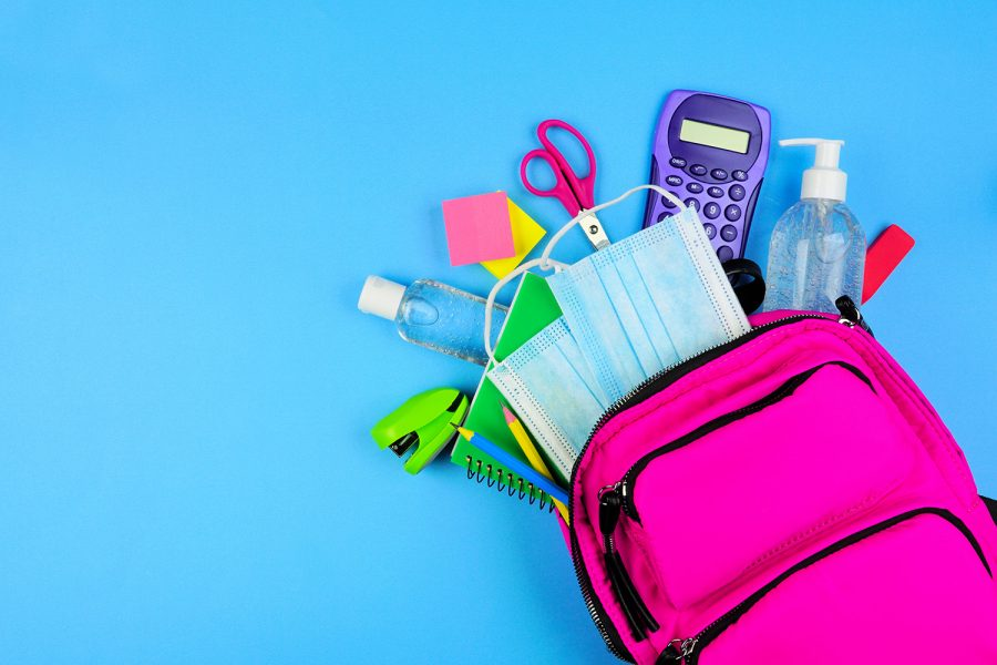 Backpack full of school supplies and COVID 19 prevention items. Top view, spilling onto a blue background. Back to school during pandemic concept.