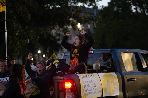 A University of Iowa gymnastics member gets pumped during the Iowa Hawkeyes homecoming parade in Iowa City on Friday, Oct. 15, 2021.