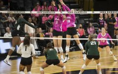 Michigan State outside hitter Biamba Kabengele hits the ball towards Iowa middle back Hannah Clayton and right side Courtney Buzzerio during a volleyball game between Iowa and Michigan State at the Carver Hawkeye Arena on Oct. 1, 2021. The Trojans defeated the Hawkeyes 3 sets to 0.