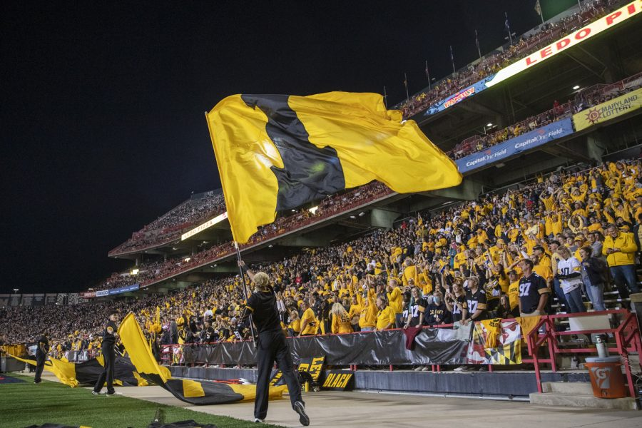 An Iowa spirit squad member lifts a flag up during a football game between Iowa and Maryland at Maryland Stadium on Friday, Oct. 1, 2021. The Hawkeyes defeated the Terrapins 51-14. (Jerod Ringwald/The Daily Iowan)