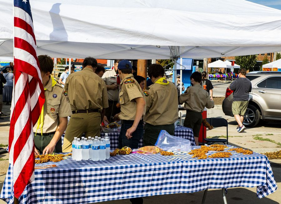 Boy Scouts from Iowa City troop 212 make pretzel necklaces at the 25th BrewFest/6th Annual Northside Oktoberfest on Saturday, Oct. 2, 2021. All money raised goes to help the troop.(Jeff Sigmund/Daily Iowan)