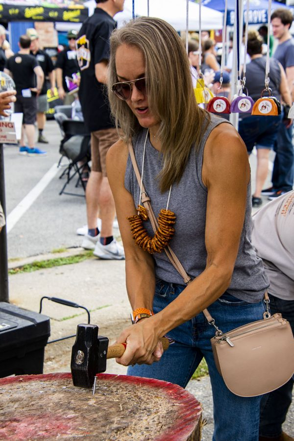 """Anna Hawken try her hand at """"Hammer Schlage"""" at the 25th BrewFest/6th Annual Northside Oktoberfest on Saturday, Oct. 2, 2021.(Jeff Sigmund/Daily Iowan)"""