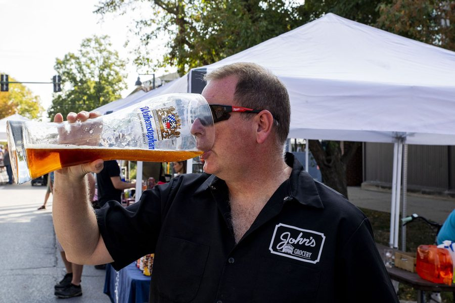 Doug Alberhasky stops to take a drink while checking to see that things are running smoothly at the 25th BrewFest/6th Annual Northside Oktoberfest on Saturday, Oct. 2, 2021. Alberhasky who is the store manage of Johns grocery and has been apart of the event for several years. (Jeff Sigmund/Daily Iowan)