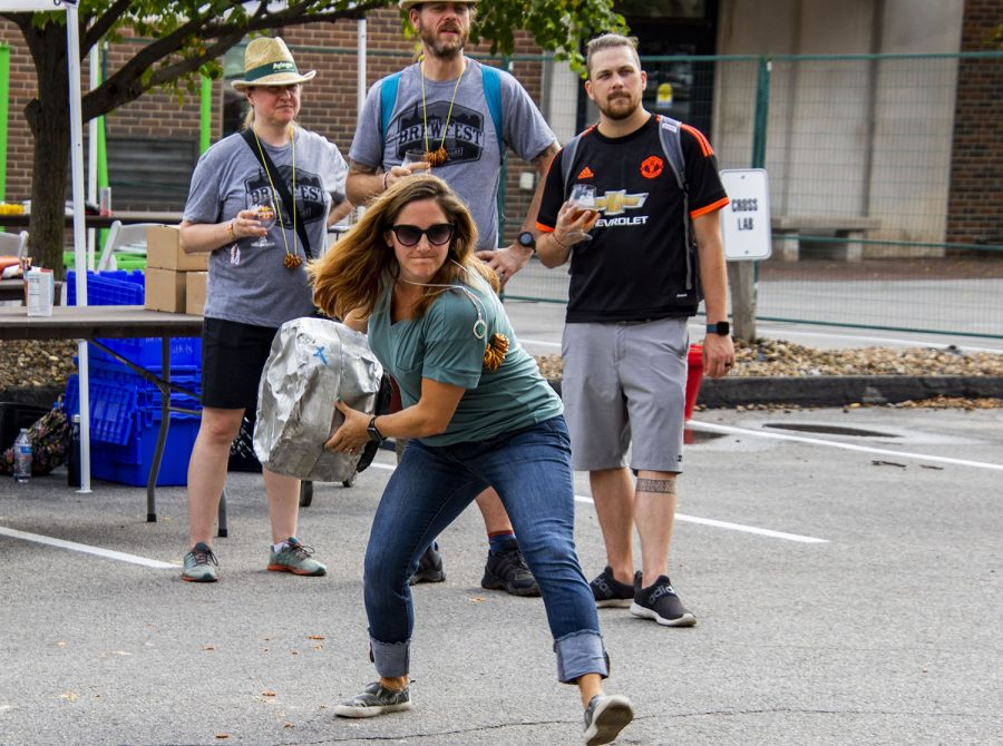 """A visitor try's her hand at """" Keg bowling"""" at the 25th BrewFest/6th Annual Northside Oktoberfest on Saturday, Oct. 2, 2021.(Jeff Sigmund/Daily Iowan)"""
