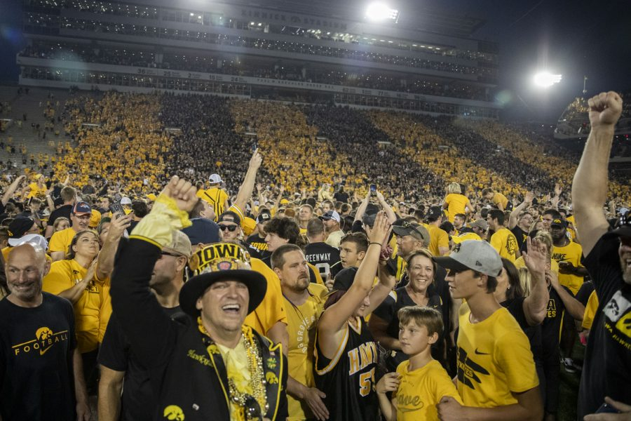 Iowa fans storm the field after a football game between No. 3 Iowa and No. 4 Penn State at Kinnick Stadium on Saturday, Oct. 9, 2021. The Hawkeyes defeated the Nittany Lions 23-20. (Grace Smith/The Daily Iowan)