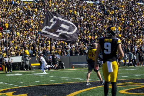 A member of the Purdue spirit squad runs a flag on the field during a football game between No. 2 Iowa and Purdue at Kinnick Stadium on Saturday, Oct. 16, 2021. The Boilermakers defeated the Hawkeyes 24-7. (Jerod Ringwald/The Daily Iowan)