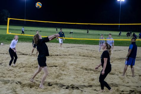 Students play volleyball at the Hawkeyes Recreational Sand Volleyball Courts on Wednesday, Oct. 21, 2021. Every Wednesday, they come together to the sand courts to play volleyball.