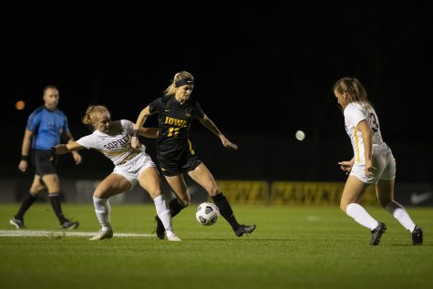 University of Iowa forward Alyssa Walker pushes University of Minnesota defender Abi Frandsen to move the ball around University of Minnesota defender Delaney Stekr during a soccer game between Iowa and Minnesota at the UI Soccer Complex on Thursday Oct. 21, 2021. The Hawkeyes defeated the Gophers 1-0.