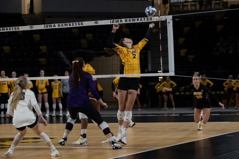 Iowa right-side hitter Courtney Buzzerio reaches for the ball during a volleyball match at Xtream Arena in Iowa City on Saturday, Oct. 16, 2021. The Wildcats defeated the Hawkeyes 3-0.