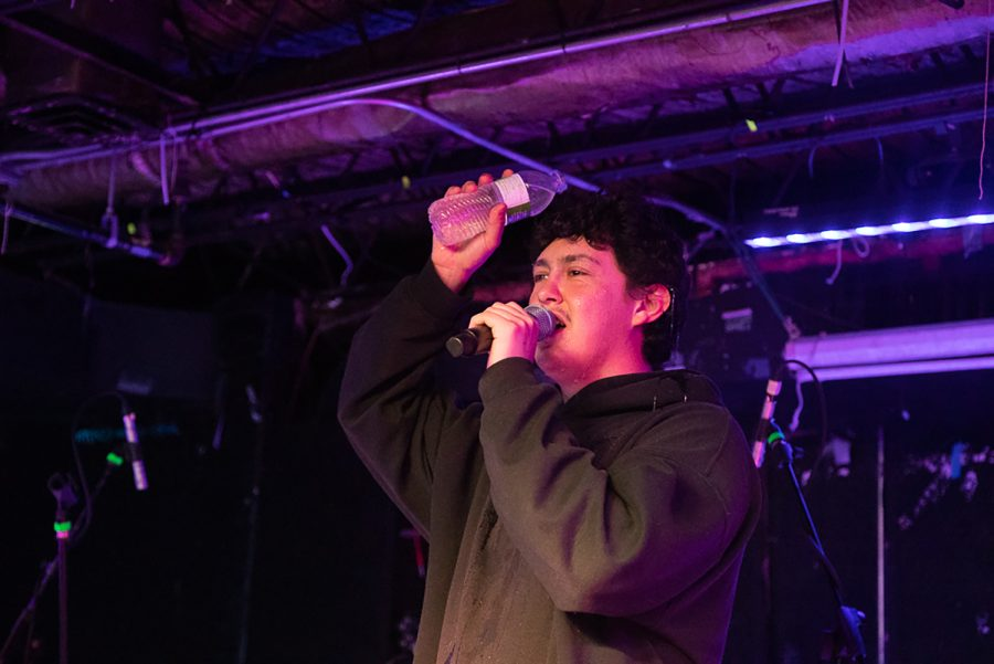 """Lead singer Frank Lopes Jr. douses himself in water to cool himself during a Hobo Johnson concert at Gabe's in Iowa City on Thursday, Oct. 14 2021. Hobo Johnson has been touring their newest record, """"Hobo Johnson Alienates His Fanbase,"""" which was released on Aug. 1, 2021. (Cecilia Shearon/The Daily Iowan)"""