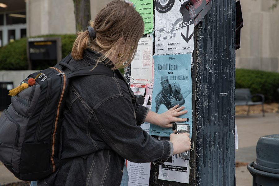 A member of SCOPE Productions is shown hanging up flyers around Iowa City on Wednesday, Oct. 13, 2021. (Larry Phan/The Daily Iowan)