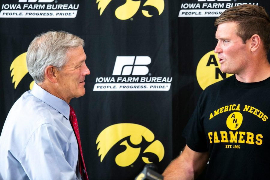 Iowa head coach Kirk Ferentz, left, shakes hands with former Iowa and NFL football offensive lineman Marshal Yanda speaks during a NCAA football news conference, Tuesday, Oct. 5, 2021, in Iowa City, Iowa