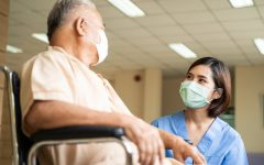 Asian nurse taking care of mature male patient sitting on wheelchair in hospital. Young woman and old man wearing surgical face mask for protection of The COVID pandemic. Girl talking to elderly man.