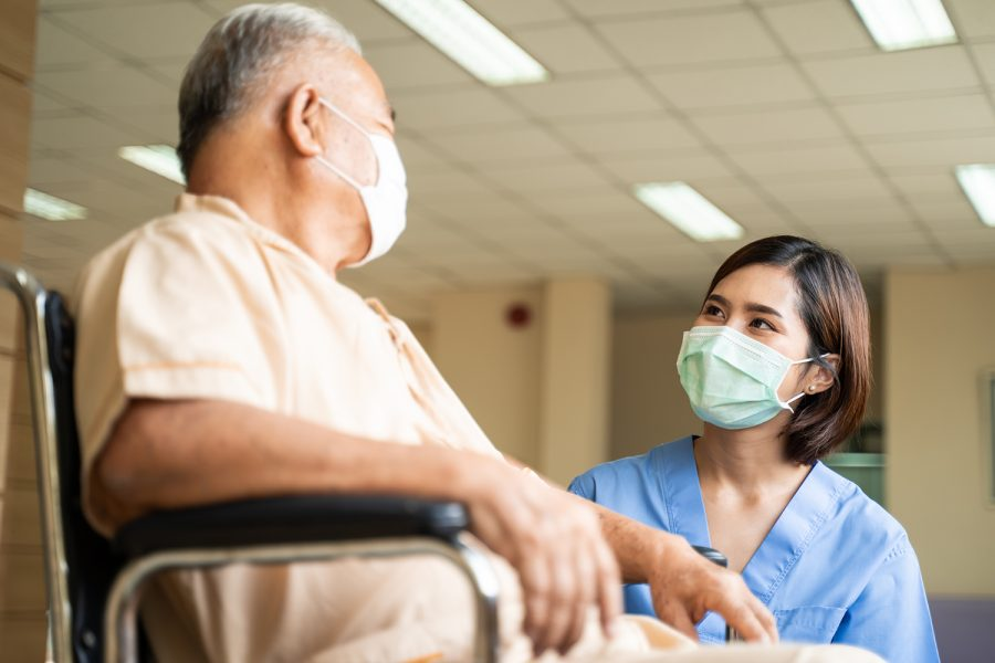 Asian+nurse+taking+care+of+mature+male+patient+sitting+on+wheelchair+in+hospital.+Young+woman+and+old+man+wearing+surgical+face+mask+for+protection+of+The+COVID+pandemic.+Girl+talking+to+elderly+man.