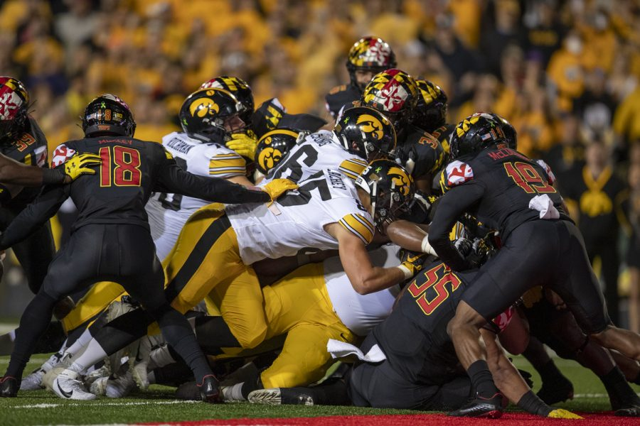 The Iowa offensive line pushes forward to get Iowa quarterback Spencer Petras into the end zone for a touchdown on a quarterback sneak play during a football game between Iowa and Maryland at Maryland Stadium on Friday, Oct. 1, 2021. The Hawkeyes defeated the Terrapins 51-14.
