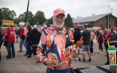 """An attendee poses with three corn dogs prior to Donald Trump's """"Save America"""" rally in Des Moines, Iowa on Saturday, Oct. 9, 2021. Two venders were in charge of feeding the thousands of attendees that showed up for Trump's rally."""