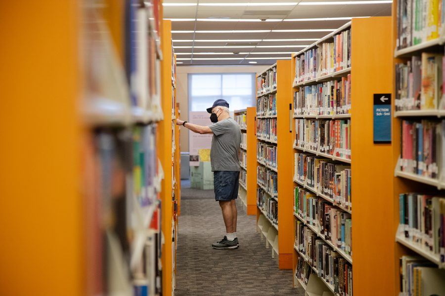 A visitor picks out a book at the Iowa City Public Library on Monday, Sept. 27, 2021.